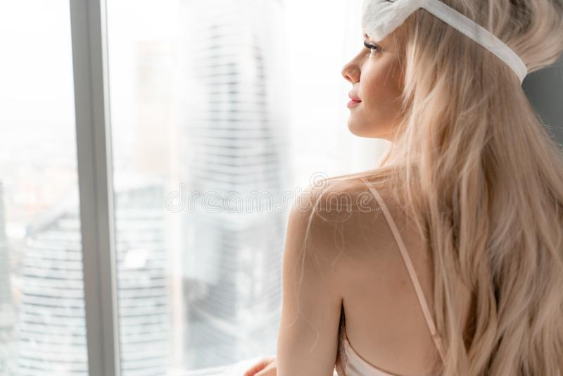 Ochtend in hotelruimte De jonge vrouw zit op comfortabel bed in masker voor het slapen op hoofd Venster van een wolkenkrabber  royalty-vrije stock afbeelding