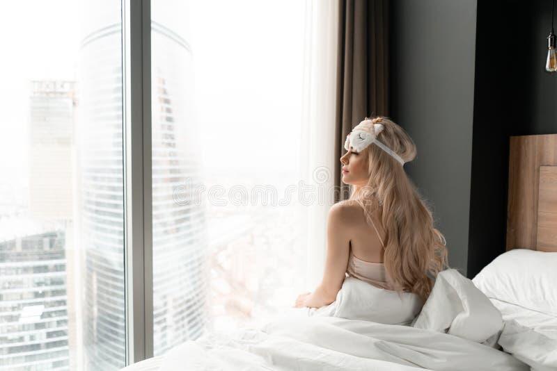 Ochtend in hotelruimte De jonge vrouw zit op comfortabel bed in masker voor het slapen op hoofd Venster van een wolkenkrabber  stock foto's