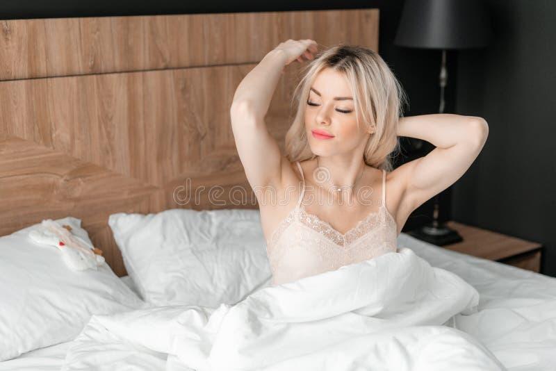Ochtend in hotelruimte Het jonge vrouwenkielzog omhoog, zit op comfortabel bed Houten hoofdeinde op achtergrond stock fotografie