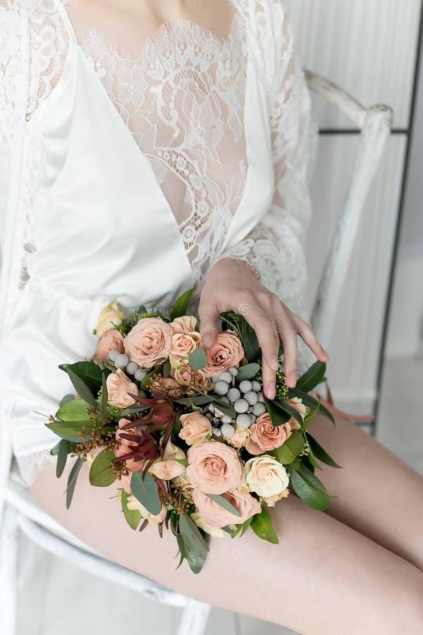 Ochtend mooie gevoelige bruid met sexy kort haar met een kleine het ondergoedzitting van de kroonzijde op een stoel met een huwel stock foto