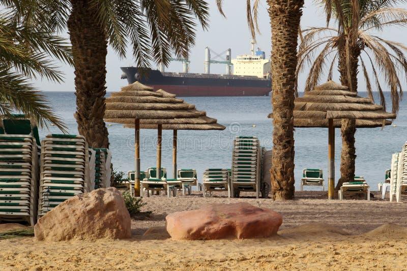 Ochtend op het openbare strand van Eilat Groot Vrachtschip op horizon stock afbeelding