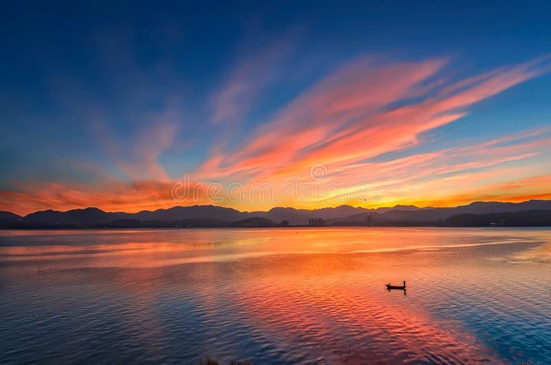 Ochtend roze die wolken in het water worden weerspiegeld stock afbeeldingen