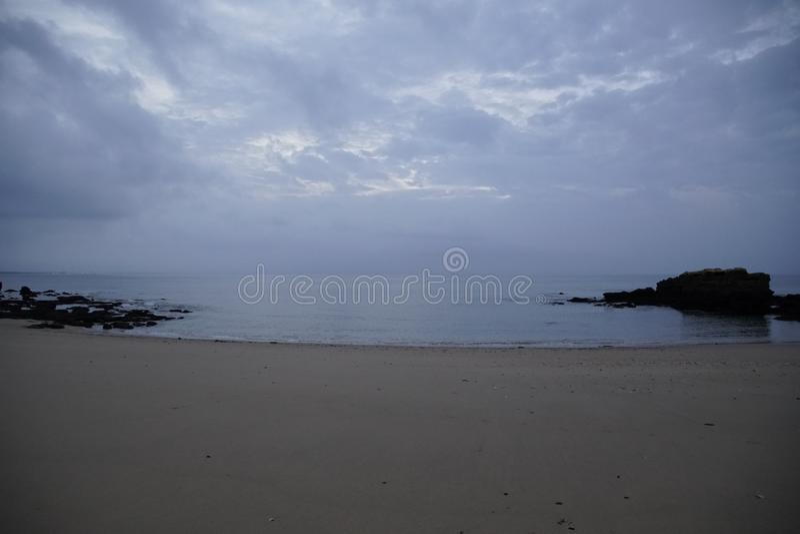 Ochtend vóór zonsopgangzon over de oceaan Strand, brandingsgolven en wolken in de ochtendhemel royalty-vrije stock afbeeldingen