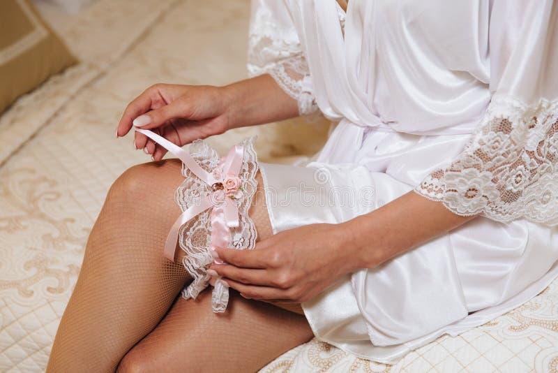 Ochtend van de Bruid Close-up van jonge bruid in roze peignoir die op witte kouseband bij de huwelijksdag zetten Handen van royalty-vrije stock afbeeldingen