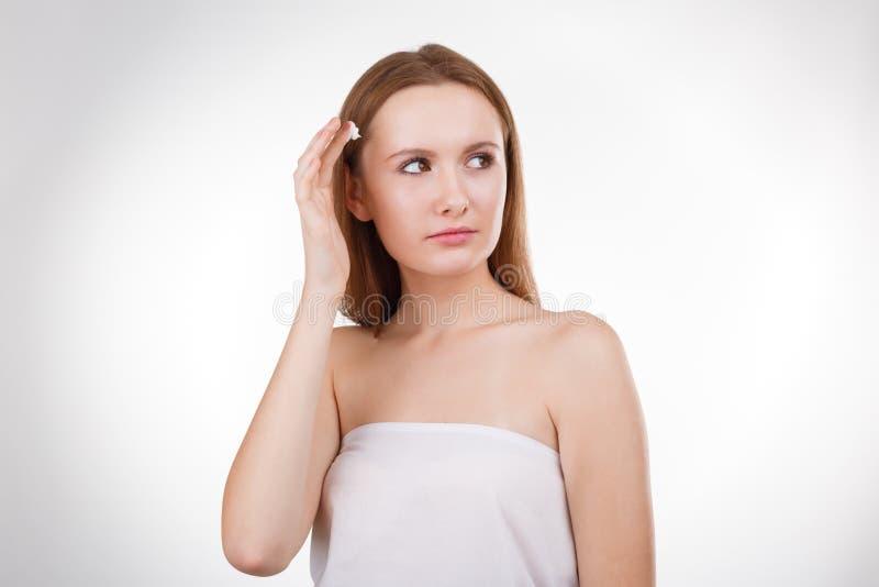 Ochtendbehandeling Jonge dame die room op haar gezicht toepassen stock fotografie