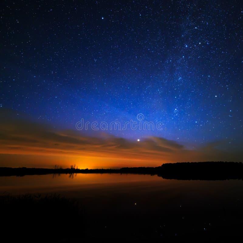Ochtenddageraad op sterrige hemel als achtergrond die in het water wordt weerspiegeld stock fotografie