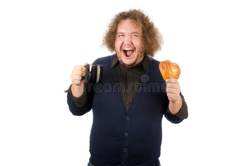 Ochtendkoffie, lunch Grappige vette mens met een mok en een broodje Het ontbijt is hete broodje en koffie royalty-vrije stock afbeelding