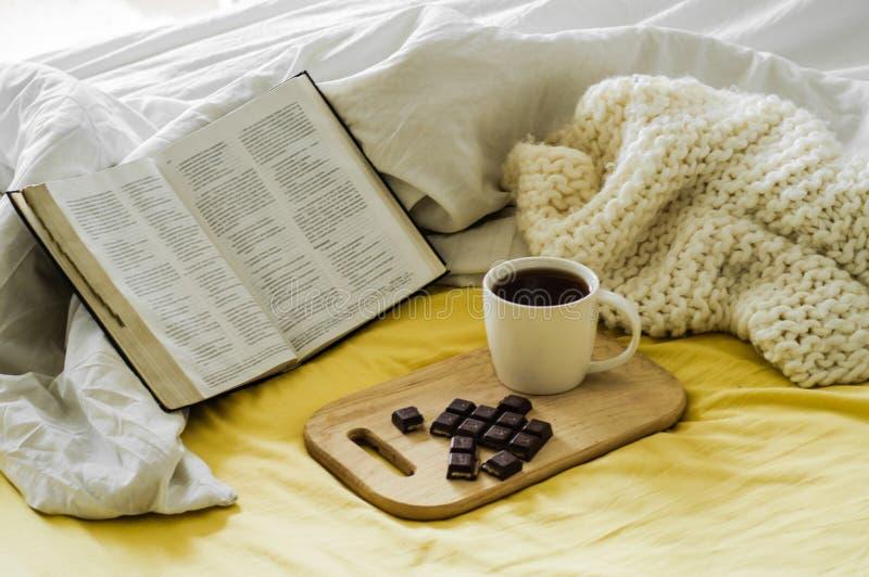 Ochtendkoffie met Bijbel die door Zonlicht wordt verlicht Kop van koffie met Christian Bible Witte slaapkamer Chocolade en koffie stock afbeelding