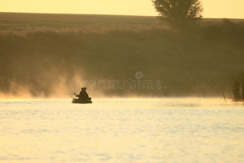 Ochtendlandschap met mist op meer met twee vissers in boot met hengels voor visserij royalty-vrije stock foto's