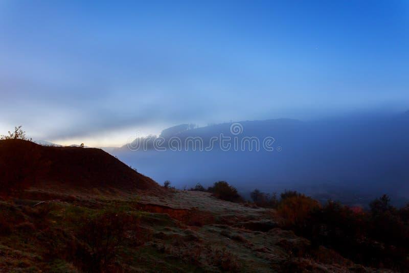 ochtendmist op een hellingsweide dichtbij bergdorp bij nacht in maanlicht royalty-vrije stock foto's
