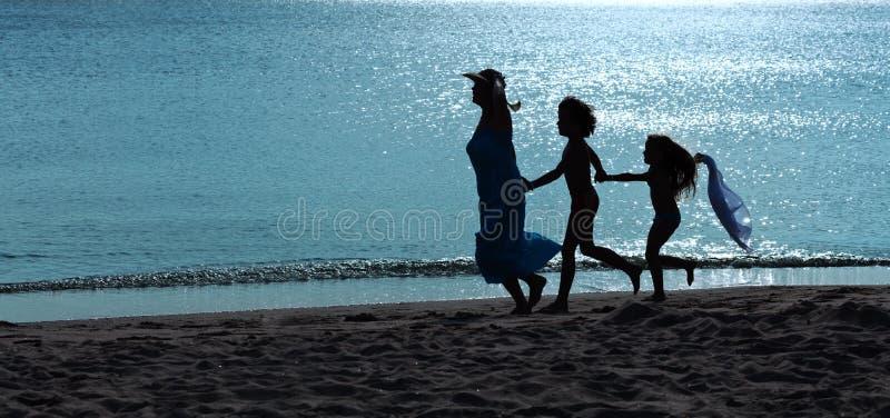 Ochtendoefening - vrouw en jonge geitjes die op het strand lopen stock afbeeldingen