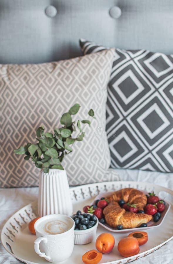 Ochtendontbijt in bed, kop van koffie, croissants, verse bessen, pot met succulent stock fotografie