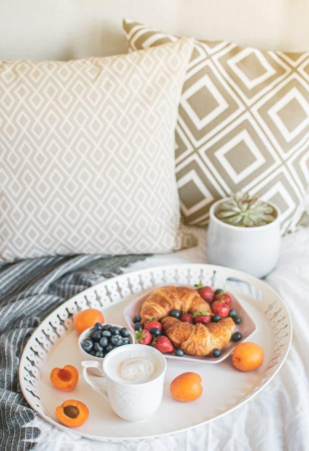 Ochtendontbijt in bed, kop van koffie, croissants, verse bessen, pot met succulent stock foto