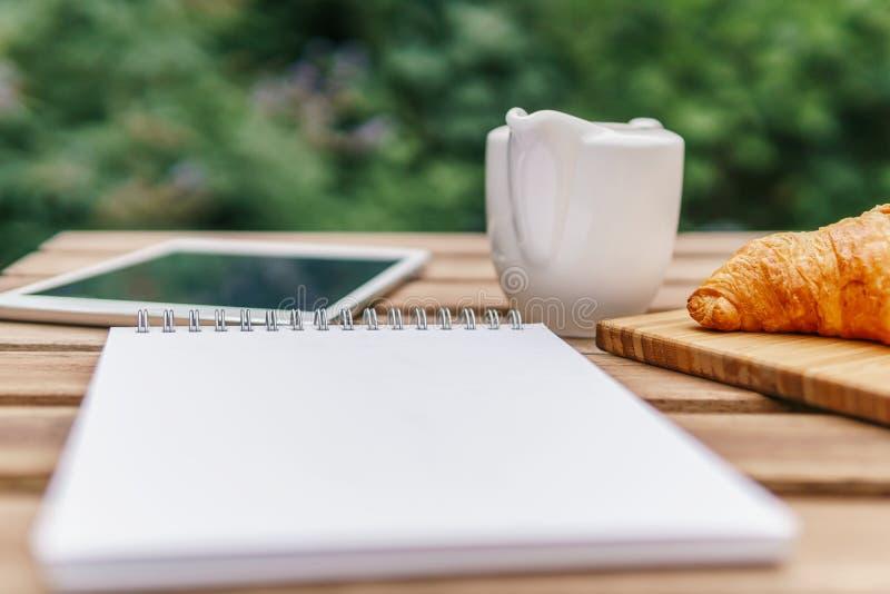 Ochtendontbijt in Groene Tuin met Frans Croissant, Koffiekop, Jus d'orange, Tablet en Nota'sboek op Houten Lijst royalty-vrije stock foto