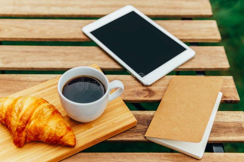 Ochtendontbijt in Groene Tuin met Frans Croissant, Koffiekop, Jus d'orange, Tablet en Nota'sboek op Houten Lijst stock afbeelding