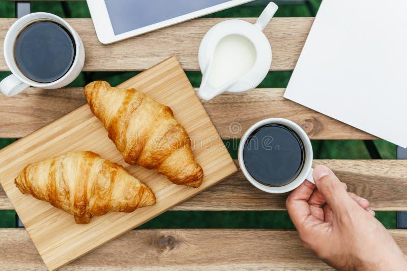 Ochtendontbijt in Groene Tuin met Frans Croissant, Koffiekop, Jus d'orange, Tablet en Nota'sboek op Houten Lijst royalty-vrije stock fotografie