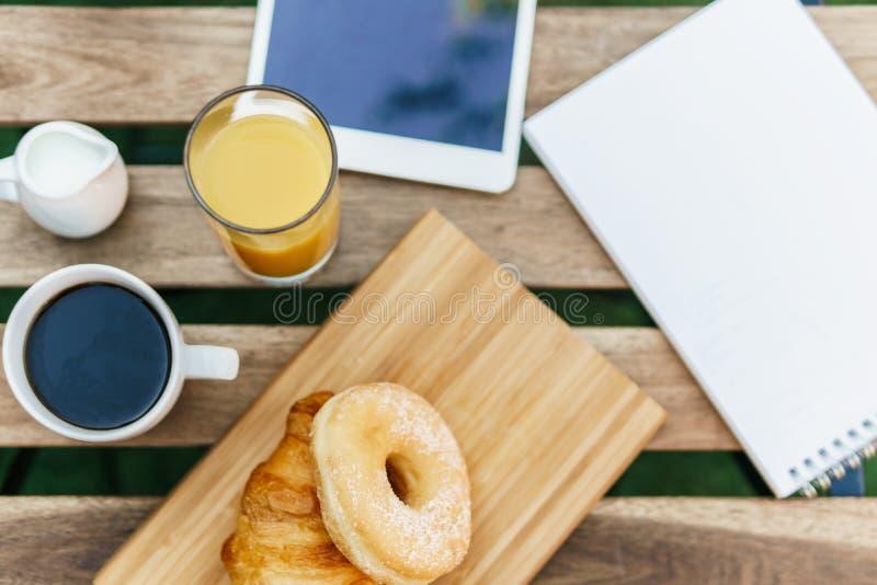 Ochtendontbijt in Groene Tuin met Frans Croissant, Koffiekop, Jus d'orange, Tablet en Nota'sboek op Houten Lijst royalty-vrije stock foto's