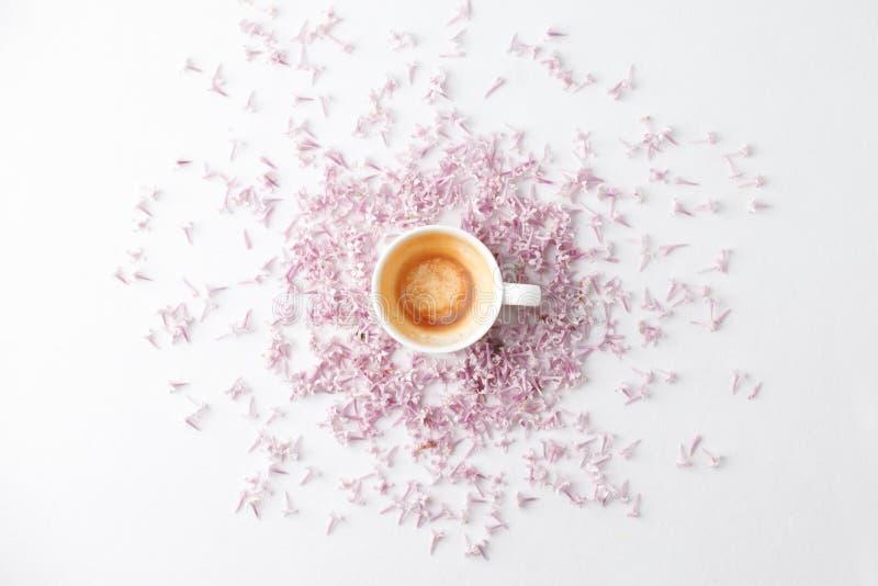 Ochtendontbijt met lege koffiekop, lilac bloemen op witte achtergrond Vlak leg, de hoogste achtergrond van meningsvrouwen Minimaa royalty-vrije stock foto