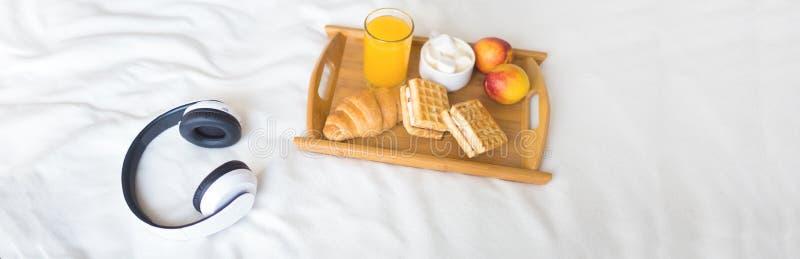 Ochtendontbijt op het witte bed Tray Croissant Coffee Waffles Juice royalty-vrije stock afbeeldingen