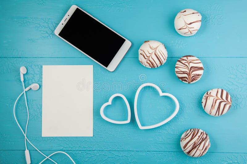 Ochtendontbijt voor Valentijnskaartendag Smartphone, chocoladesuikergoed, kaart voor tekst, twee decoratieve harten op blauwe ach stock afbeelding