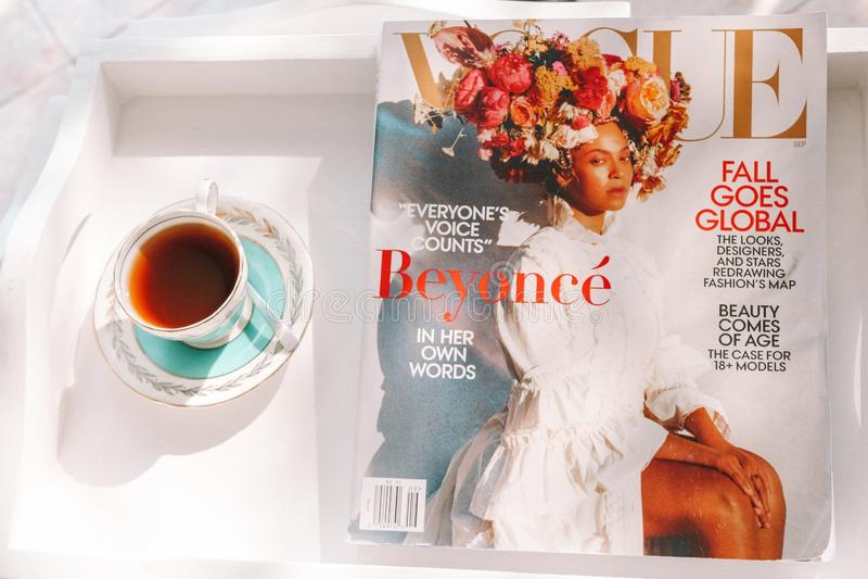 Ochtendthee in Uitstekende Theekop met Vogue-Tijdschrift Beyonce en Wit Dienblad stock afbeelding