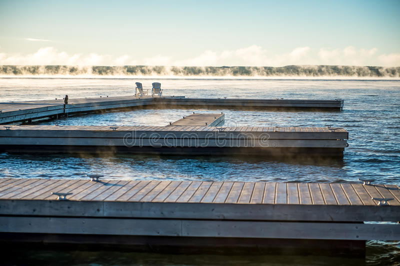 Ochtendzonsopgang op een dok met de Stoelen en de mist van Muskoka stock fotografie