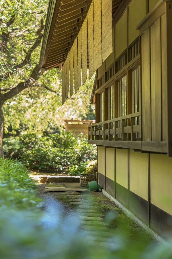 Ocieniony herbaciany dom wykładał z kółkową kamienną ścieżką z trzcinowym cano zdjęcia stock