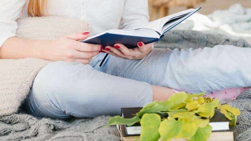 Ocio acogedor del hogar de la comodidad de la cama del libro de lectura de la mujer imágenes de archivo libres de regalías