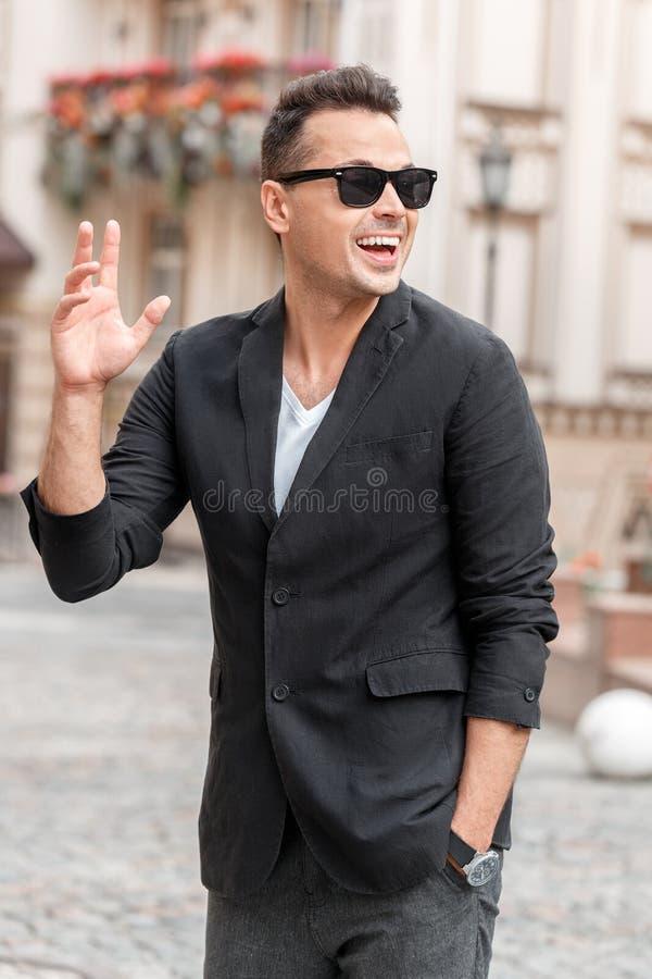 Ocio del aire libre Hombre joven y gafas de sol en la situación del traje en la calle de la ciudad que agita a la sonrisa del ami fotografía de archivo libre de regalías