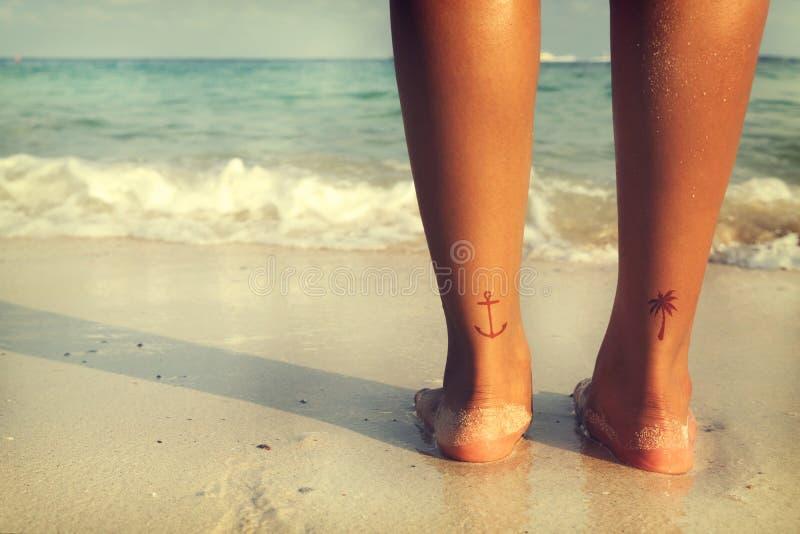 Ocio en verano - la parte posterior del moreno hermoso de las mujeres se relaja en la playa con el tatuaje a pie fotos de archivo