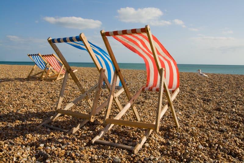 Ocioso del sol de la silla de cubierta en día ventoso de la playa foto de archivo libre de regalías