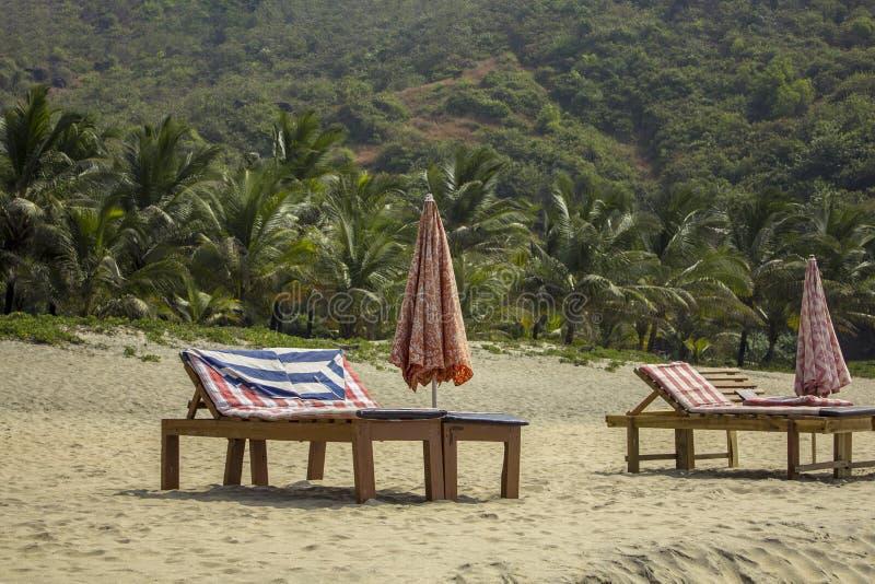 Ociosos vacíos de la playa con los colchones y los paraguas soleados doblados en la arena blanca contra el contexto de la selva v foto de archivo libre de regalías
