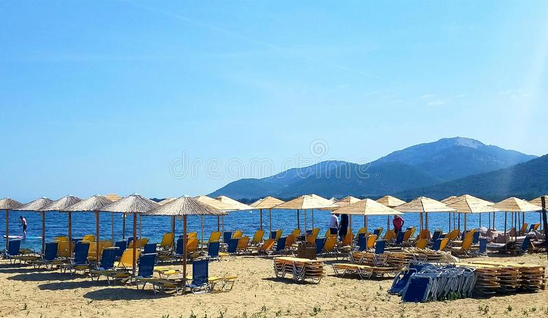 Ociosos y paraguas de Sun que esperan fabricantes del día de fiesta en una playa en Grecia fotografía de archivo libre de regalías