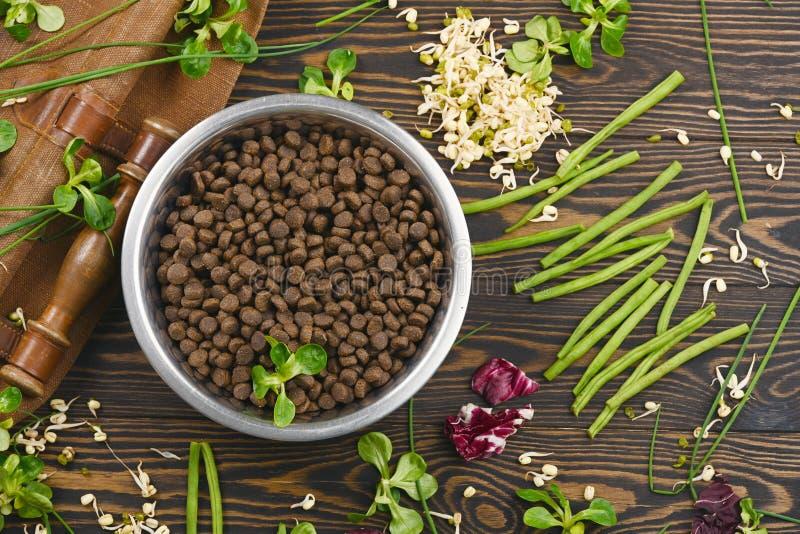 Особенный корм для домашних животных vegan и естественные сырцовые ингредиенты на коричневой деревянной предпосылке стоковая фотография