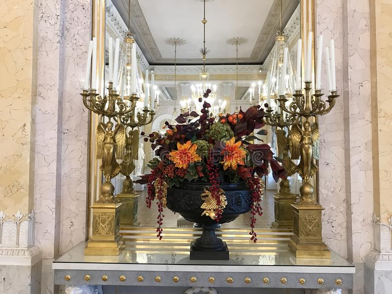 Bouquet and candelabras in Habsburg state rooms, Albertina Museum, Vienna. Oct 2017: Beautifully arranged flower bouquet surrounded by candelabras decorates a royalty free stock photo