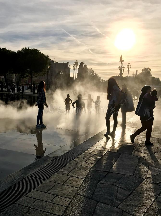 Children playing in fountain seen in silhouette in Nice, France stock photography