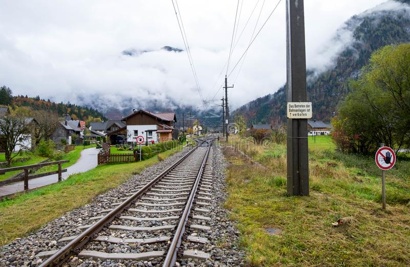 Railway across middle of Obertraun town. The weather was so cloudy and ready to rain any times. Oct 22, 2017 - Obertraun, Austria: Railway across middle of stock image
