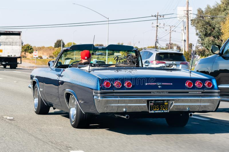 Oct 26, 2019 San Francisco / CA / US - 1965 Chevrolet Impala SS driving on the freeway; Frisco`s Finest car club logo displayed o royalty free stock images