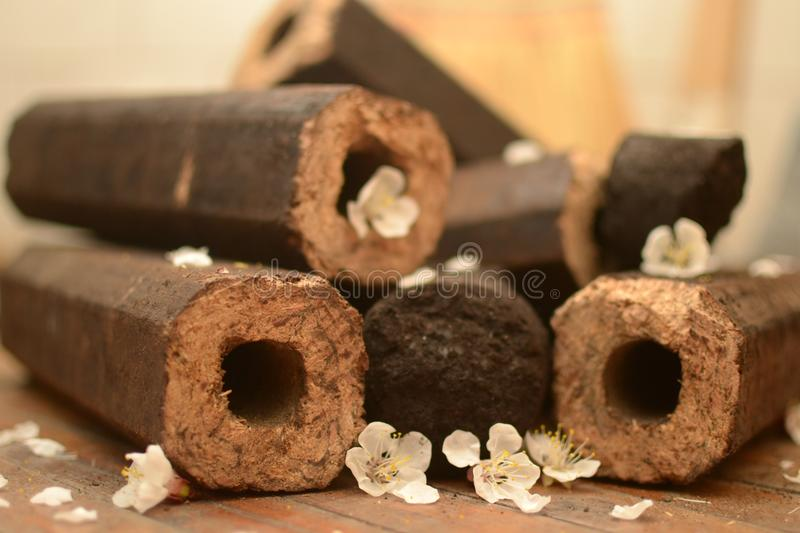 Octagonal brown briquette with a hole. Brown briquette octagonal witha a hole and worth of coal in a heap on the floor with petals of white flovers and a broom royalty free stock image