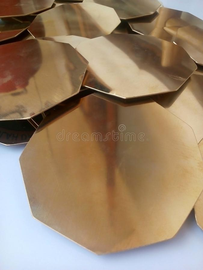 Octagonal shaped brass metal pieces on white background royalty free stock photos