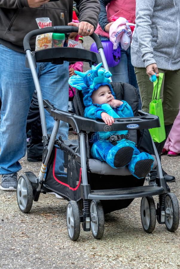 October 27, 2018 Coloma MI USA; a cute little baby in a blue dinosaur costume enjoys being pushed in his stroller at an outdoor. Halloween event stock photos