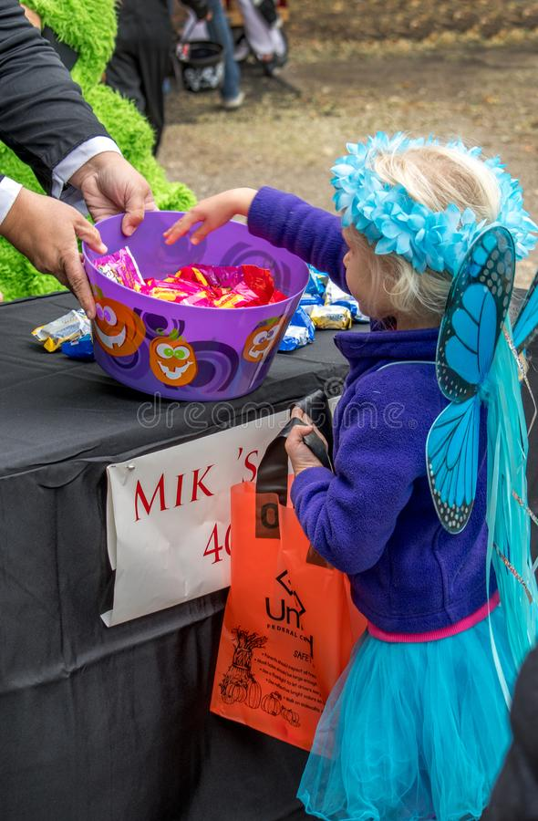 little girl dressed as a fairy takes candy during an outdoor Halloween event stock photo