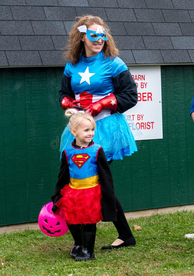 A mother and daughter dress in super women costumes during a Halloween event royalty free stock image