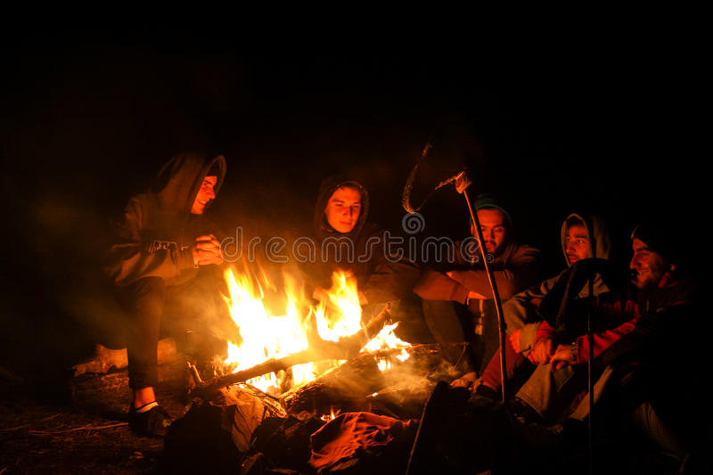 October 2014: group of friends laughing and sitting at camp fire after long autumn mountain hike stock image
