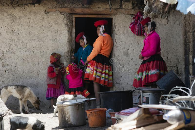 Quechua Indian Woman And Her Family Dressed In Colorful Handwoven Outfit And Standing Outside Their House. October 21, 2012 - Maras, Urubamba Valley, Peru royalty free stock photo