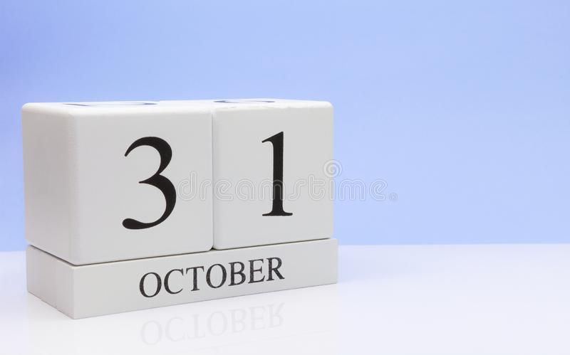 October 31st. Day 31 of month, daily calendar on white table with reflection, with light blue background. Autumn time, empty space stock photography