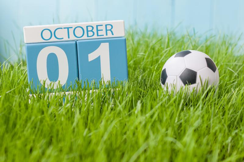 October 1st. Day 1 of month, color calendar on green grass background with a ball. Autumn time. Football and soccer play royalty free stock images