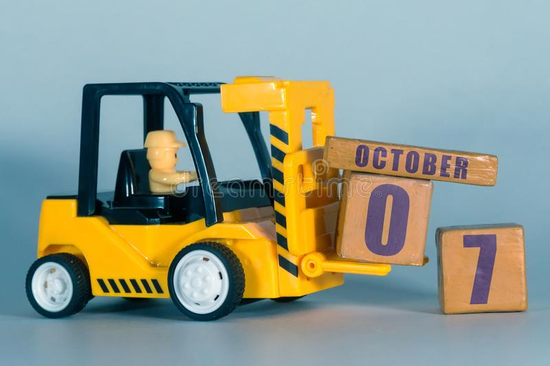 October 7th. Day 7 of month, Construction or warehouse calendar. Yellow toy forklift load wood cubes with date. Work planning and. Time management. autumn month royalty free stock photography