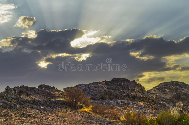 Rocky hill in Haiil, Saudi Arabia. October, 20th 2018, Rocky hills mountains in the foreground and clouds with sun rays in background. Hail, Saudi Arabia royalty free stock image