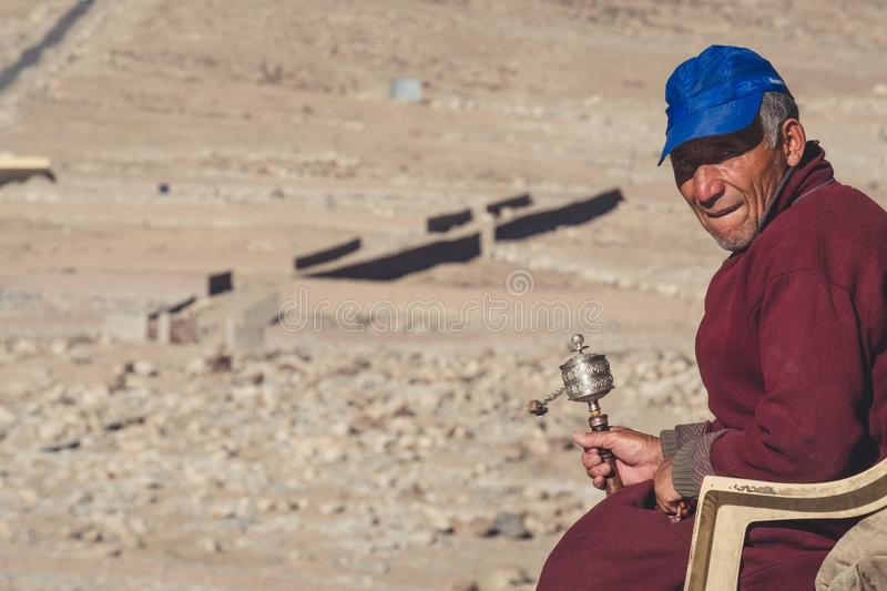 October 17th 2017 : A Tibetan Buddhist monk sitting and holding a wheel prayer with desert background in Ladakh stock photos